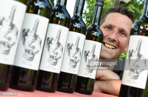 Vintner Fred Strieth from the Thilo Strieth vineyard presents bottles of his Blanc de Noirs 2014 whose label features a raised middle finger and the...