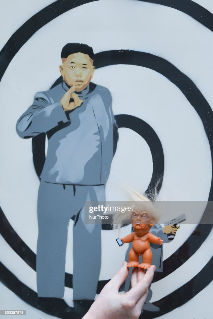 A vinyl doll which features President Donald Trump, made by a former sculptor for Disney, Chuck Williams, placed near a satiric painting of supreme leader of North Korea, Kim Jong-un, painted by Irish artist Solus. Donald Trump Troll dolls can be seen and bought at Balla Ban Art Gallery in Dublin city center. On Wednesday, 24 October 2017, in Dublin, Ireland.