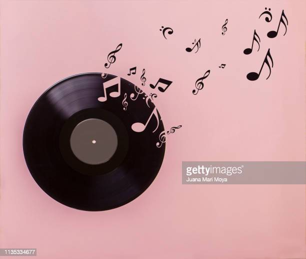 vinyl record on pink background. several musical notes are born of the vinyl record - note de musique photos et images de collection