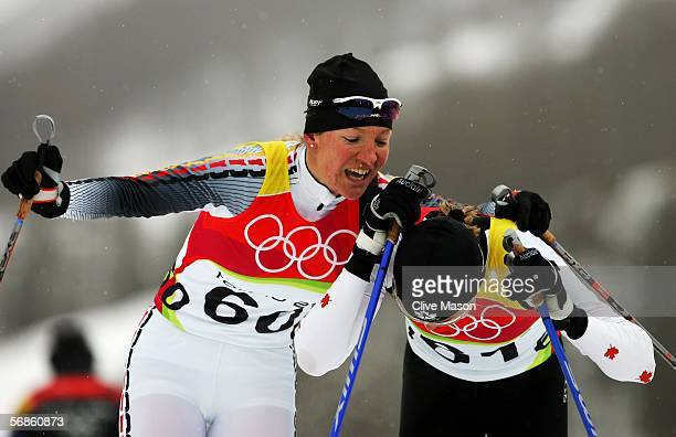 Viola Bauer of Germany embrasses Sara Renner of Canada after crossing the finish line in the Womens Cross Country Skiing 10km Interval Start Final on...