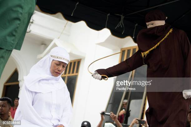A violator during punishment in front of public in a yard of mosque in Aceh province Indonesia Today five violators of sharia law were punished two...