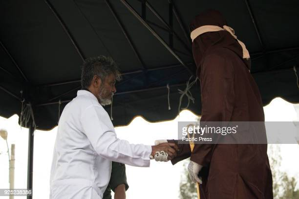 A violator shake hands with executioner after endure flogged punishment in front of public in a yard of mosque in Aceh province Indonesia Today five...