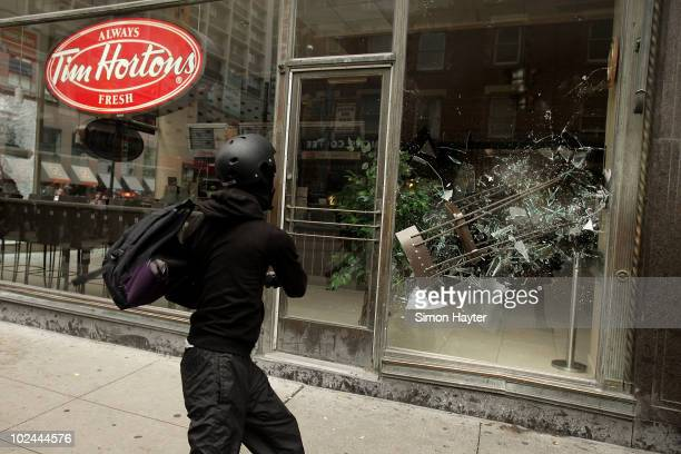 A violent antiG20 protester using Black Bloc tactics throws a chair through the window of a Tim Hortons while demonstrators smashed their way through...