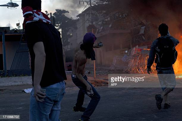 Violent demonstrators burn objects and clash with the police during a protest outside the Mineirao stadium in Belo Horizonte on June 26 2013 where...