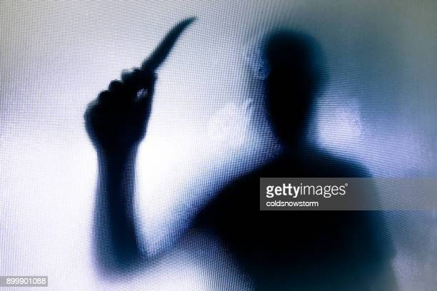 violent threatening silhouette of man wielding a knife behind frosted glass window - murder stock pictures, royalty-free photos & images