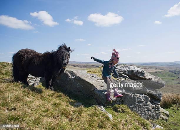 Violet Owen daughter of the Yorkshire shepherdess Amanda Owen plays on rocks as her mother feeds the horses at Amanda's farm Ravenseat on April 15...