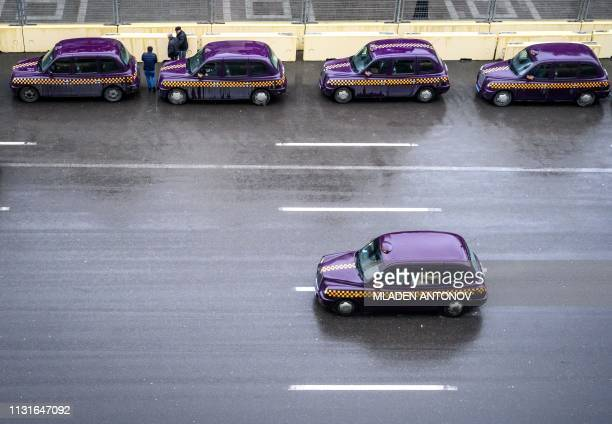 Violet painted Londonstyle taxi cabs wait for customers outside a shopping center in central Baku on March 20 2019 Some 1000 of the iconic 'black...