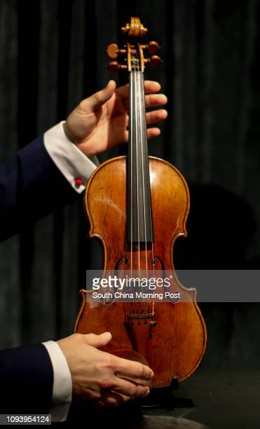 Violin expert Paul Hayday plays a rare 1684 violin known as the ExCroall McEwen by Antonio Stradivari estimated at HK$1219 million at Sotheby's Hong...