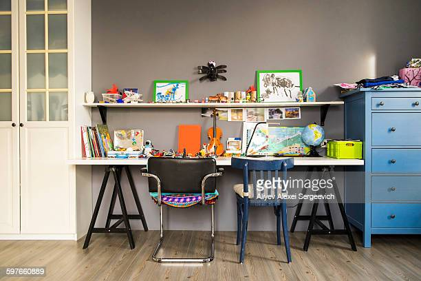 violin, globe, paintings and books on childs desk and shelves - tidy room stock pictures, royalty-free photos & images