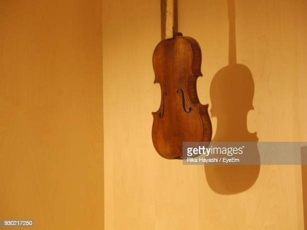 violin hanging on yellow wall - cremona stock pictures, royalty-free photos & images