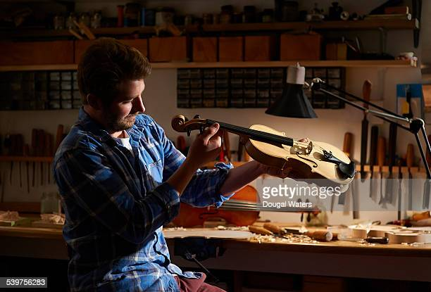 violin maker checking his work. - violin stock pictures, royalty-free photos & images