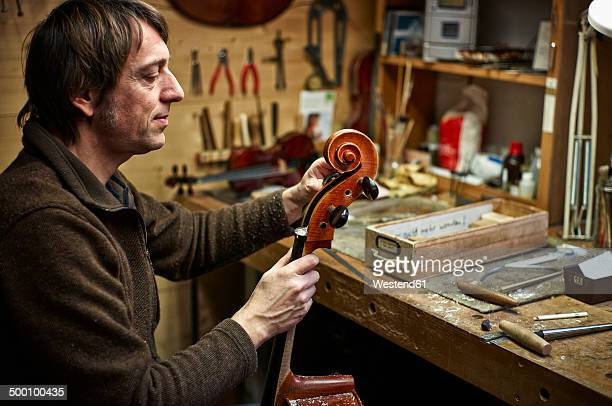Violin maker in his workshop adjusting a cello mechanism