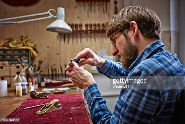Violin maker in his workshop examining neck of an instrument