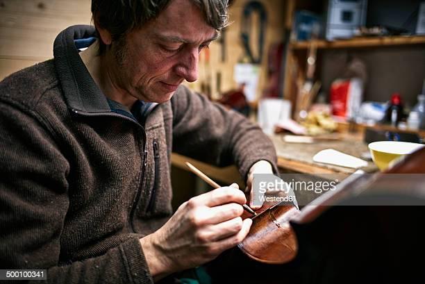 Violin maker repairing crack in cello
