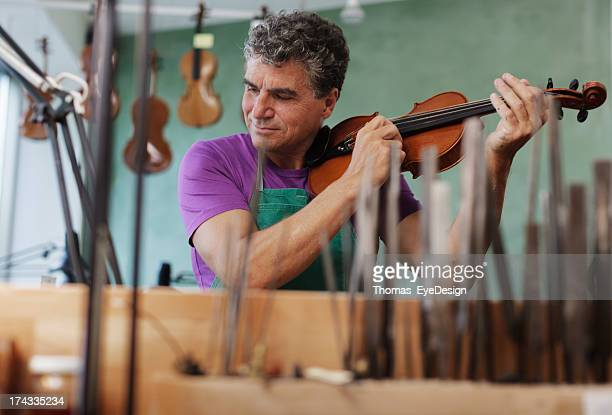 violin maker testing an instrument - instrument maker stock photos and pictures