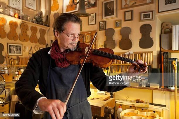 violin maker tuning an instrument