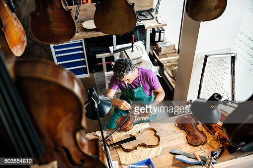 Violin Maker Working On Instrument