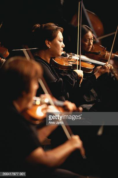 Violin section performing in orchestra (focus on woman)