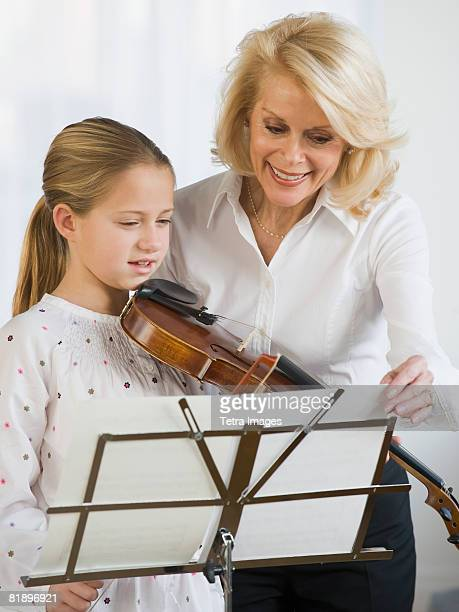 Violin teacher and student looking at sheet music