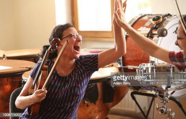 Violin teacher Deborah Strauss highfives violinist Mark Kovnatskiy during Yiddish Summer Weimar on July 27 2018 in Weimar Germany The annual fiveweek...
