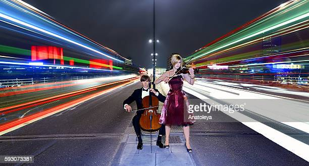 Violinist and cellist performing in traffic