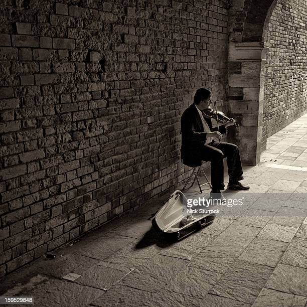 CONTENT] A violinist busks in an alleyway in Venice's backstreets