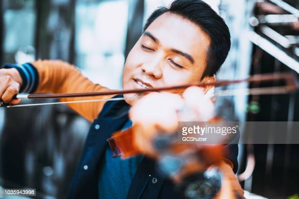 violinist enjoying his art - entertainment occupation stock pictures, royalty-free photos & images