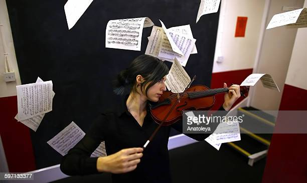 violinist & floating pages - sheet music stock photos and pictures