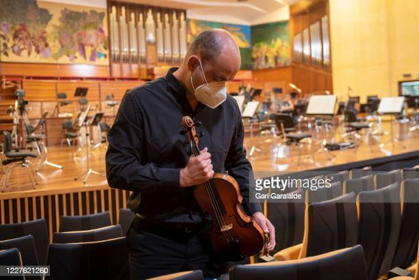 Violinist from the Basque Symphony Orchestra prepares the violin to play in a concert that will be broadcast by public television on May 28, 2020 in...