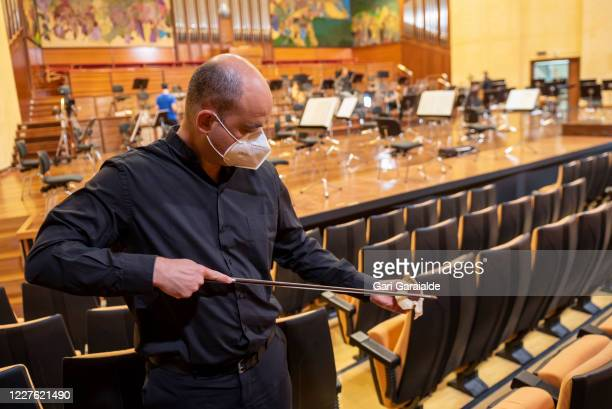 A violinist from the Euskadi symphony orchestra prepares the violin bow to play in a concert to be broadcast on Basque public television on May 28...