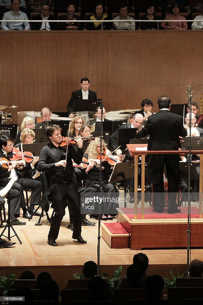 Violinist Joshua Bell (L) and conductor Jahja Ling (R) with the San Diego Symphony perform on the stage in concert at Shanghai Oriental Art Center on November 5, 2013 in Shanghai, China.