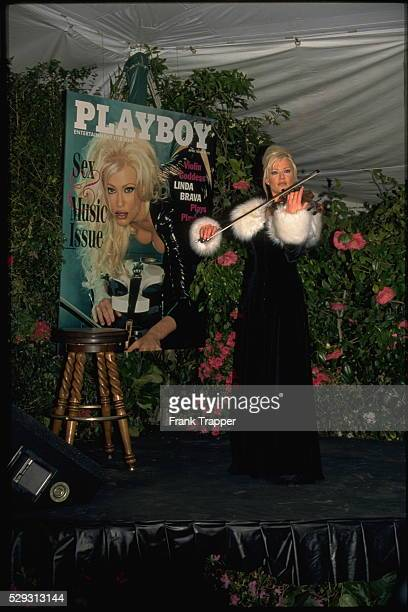 Violinist Linda Brava plays her instrument before an enlargement of the Playboy cover of the issue in which she appears