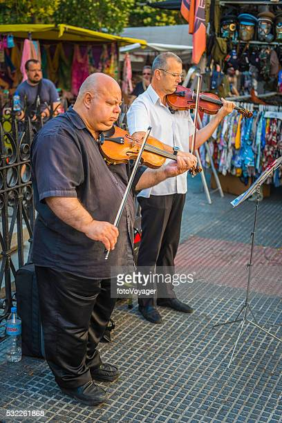 Violinist musician buskers performing in El Rastro market Madrid Spain