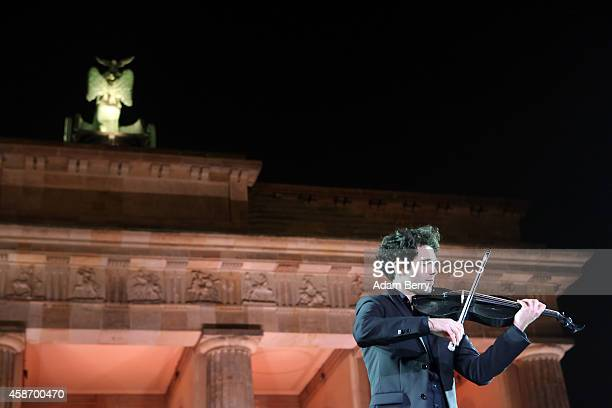 A violinist performs during celebrations for the 25th anniversary of the fall of the Berlin Wall at the Brandenburg Gate on November 9 2014 in Berlin...