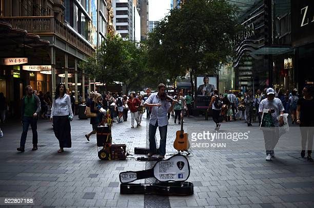 A violinist performs in a shopping arcade in the central business district of Sydney on April 21 2016 The Reserve Bank has slashed rates by 275 basis...