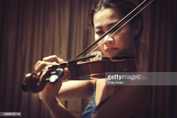 violinist playing music on stage - violin stock pictures, royalty-free photos & images