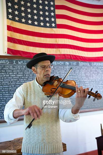 Violinist playing violin at Vermilionville history museum of Acadian Creole Native American cultures Lafayette Louisiana USA
