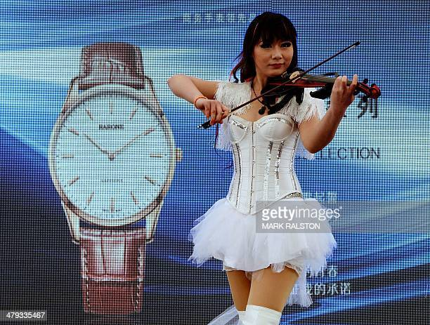 A violinist plays during a watch promotion at the Wangfujing shopping street in Beijing on March 18 2014 China's yuan weakened against the dollar...