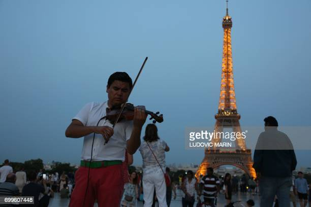 A violinist plays on Trocadero plaza in front of the Eiffel tower in Paris during the annual 'Fete de la Musique' at night on June 21 2017 / AFP...