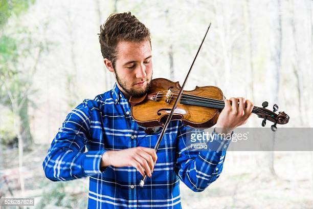 Violinista en práctica en frente de la ventana