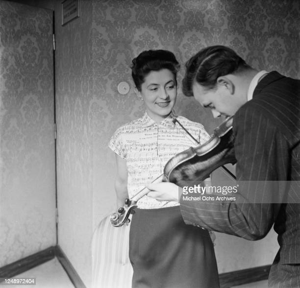 Violinist reads sheet music from the Waltz blouse, created by Viennese fashion house Neumann, 14th April 1952. The cotton blouse is printed with some...
