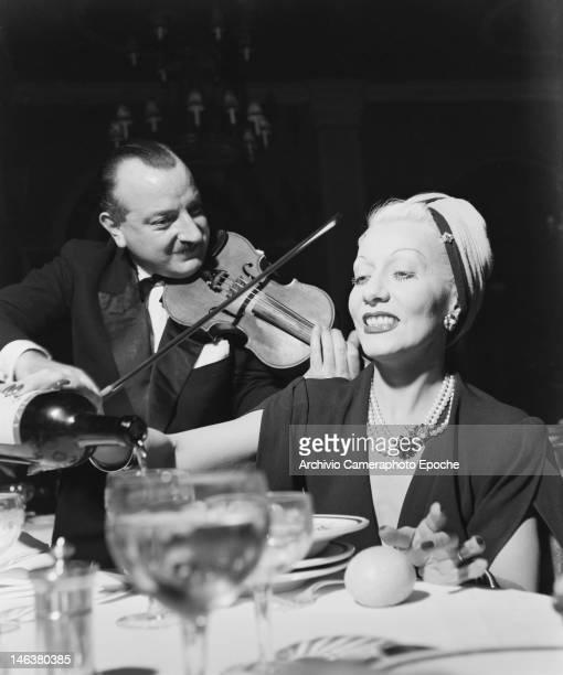 A violinist serenades a guest at the Black White Festival in Sanremo Italy circa 1950