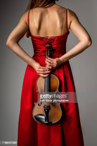 violinist woman holding violin behind - strapless dress stock pictures, royalty-free photos & images