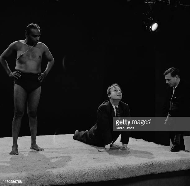 Violinist Yehudi Menuhin performing yoga poses as his guru BKS Iyengar and broadcaster David Attenborough watch for the BBC television special...