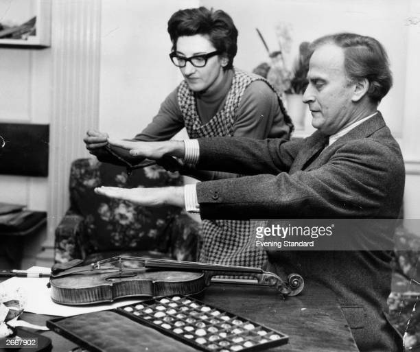 Violinist Yehudi Menuhin tries a touch of levitation over a violin assisted by a box of glass eyes and a woman who is using a small divining rod by...
