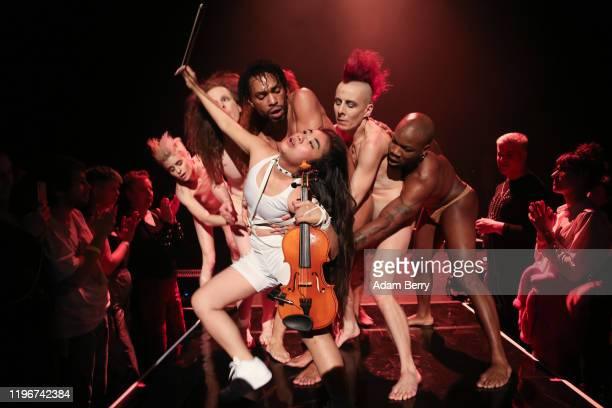 Violinist Yukari Aotani performs with dancers during the show Peaches There's Only One Peach With The Hole In The Middle by Canadian musician...