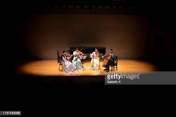 violinists and cellist playing at classical music concert - classical stock pictures, royalty-free photos & images