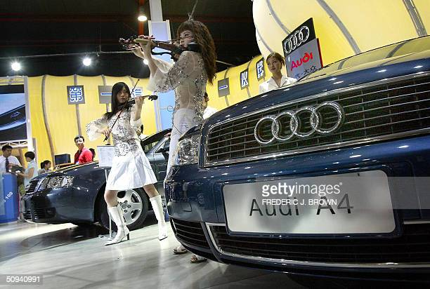 Violinists perform beside an Audi A4 at China Auto 2004 in Beijing 09 June 2004 where auto manufacturers from across the globe are in gathering this...