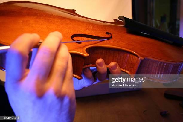 Violin-maker (luthier) checking sound post location