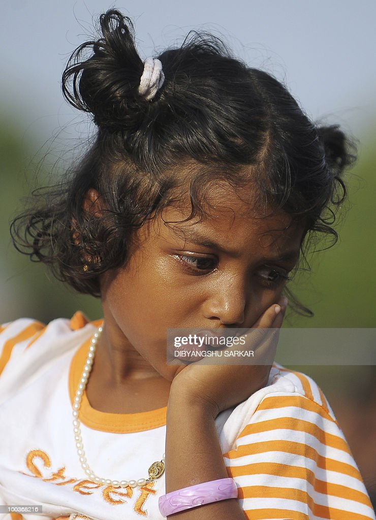 Violla, the four-year old daughter of Air India Express crash victims Naveen Walton Fernandes and Savitha Philomene D'Souza, looks on during the burial of her parents on the grounds of the Holly Cross Church in Mangalore on May 24, 2010. Investigators on May 22 widened the search for the 'black box' data recorder of an Air India Express that crashed into a gorge killing 158 people, as the airline denied lax safety claims. AFP PHOTO/Dibyangshu SARKAR